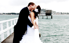 Groom kissing Bride on pier