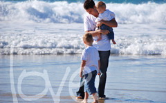 Father and young sons in family photo shoot at the beach