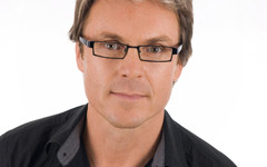 Professional head shot of handsome man in glasses