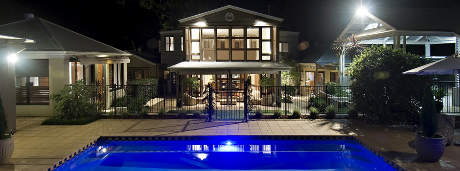 Stunning property photo at night with an inviting pool...