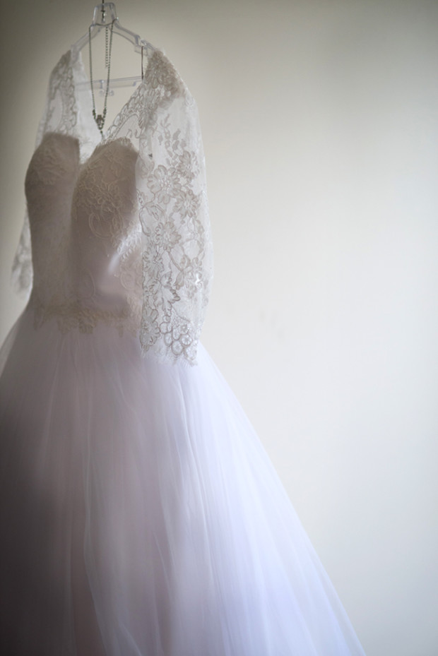 Photo of Wedding gown hanging in wardrobe